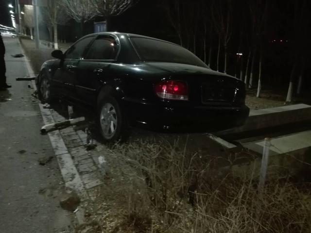 朝阳一轿车失控滑进绿地卡在甬路口