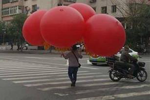 银州男子手持大气球轻巧上路 体重不够都得上天