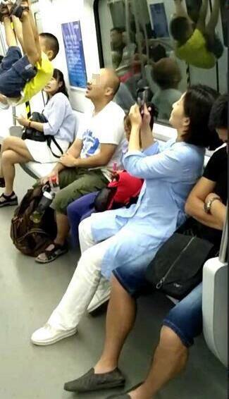 熊孩子地铁里玩吊环身体腾空 家长拍视频不阻止