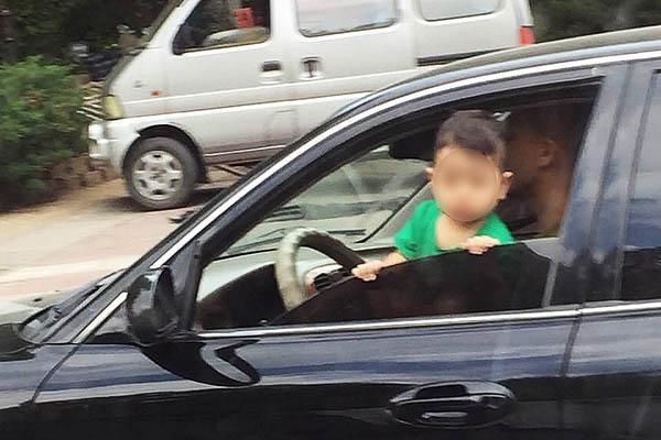 抚顺一男子抱孩子开车 孩子扒着车窗探出身子往外瞅