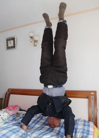 83岁的王国清老人在床上轻而易举地做了个倒立姿势.肖景昕摄