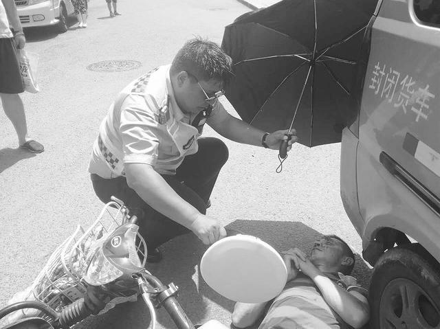 货车与两轮车相撞 交警冒酷暑为伤者撑伞遮阳
