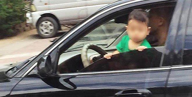 抚顺男子抱孩子开车 孩子扒车窗探出身子往外瞅