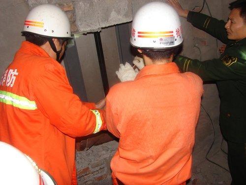 工人维修电梯被牵引机夹手 小空间里消防队员帮他脱险