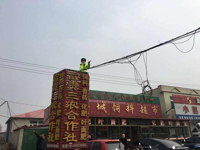 顶着6级大风 交警爬上5米高广告牌托举光缆
