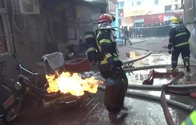 丹东一家饭店起火,消防队员徒手拎出三个喷火的煤气罐