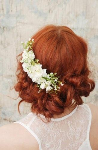 气质的一款妩媚发型,性感的自然波浪卷发可以用鲜花制成的花环来装饰.图片