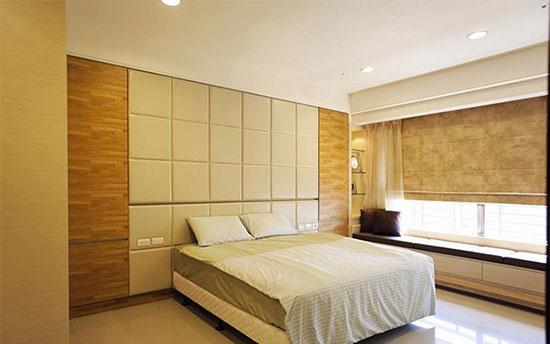 主卧延续公共区域的色彩调性,床头背墙的皮革方格设计以及木纹装饰图片