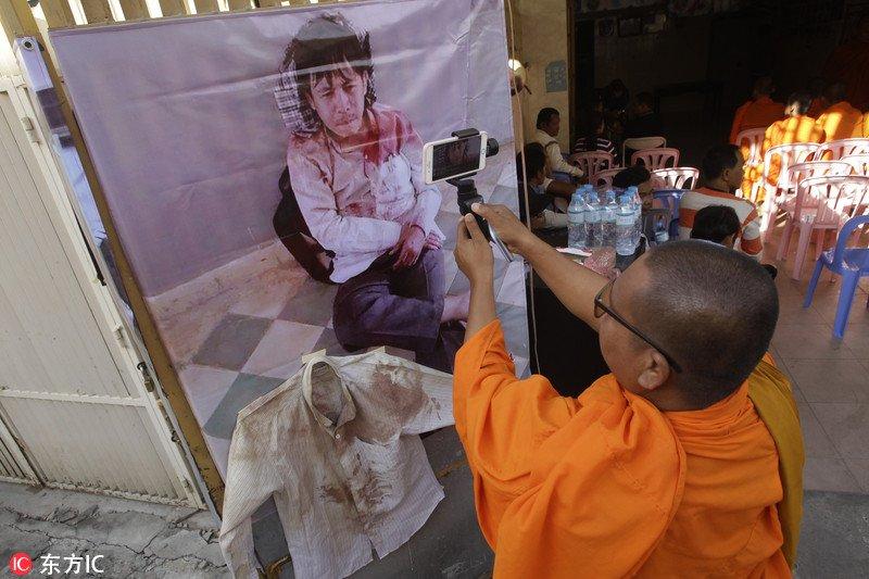 """柬埔寨和尚变身""""低头族"""" 带自拍杆参加劳工抗议纪念活动"""