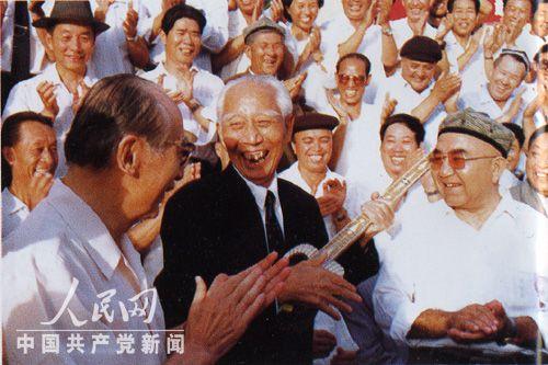 王震在新疆_1991年8月,王震在新疆喀什弹起少数民族代表送给他的冬不拉.