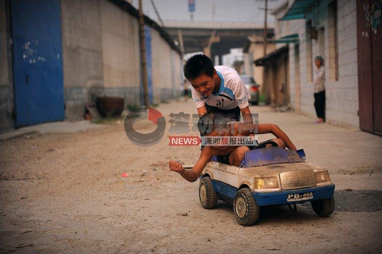 """彭志超和伙伴开着他的""""私家车""""在家门口附近兜风。不时地用手将跑偏的轮子拍正,还叫嚷着这是我的""""来斯来斯""""。他说:我的梦想就是长大后去F1开赛车去。 图/潇湘晨报记者 杨抒怀"""