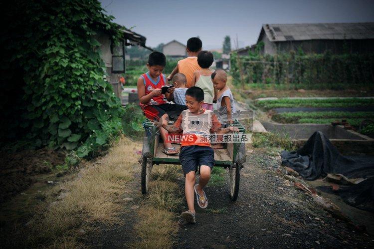 """8月8日,长沙鸭子铺,父母都出门做工去了,""""守家""""的孩子骑着三轮车远行,由于""""超重""""不时要下车推,暑假他们很少迈出鸭子铺,然而孩子发挥着自己的想想,制造着快乐。图/潇湘晨报记者 杨抒怀"""