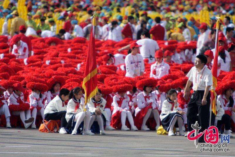 首都各界庆祝中华人民共和国成立60周年大会将于10月1日10时在北京举行。现场的学生们佩戴者红色花环。中国网/胡迪摄