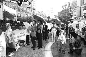 市民冒雨在街头观看阅兵式电视直播 首席记者雍和摄