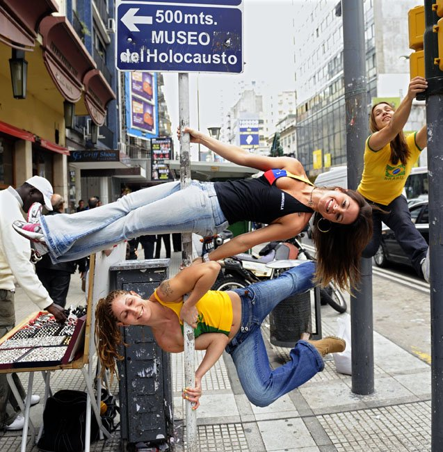 """图为街头表演的舞者将路边电线杆与路灯当做""""钢管""""。"""