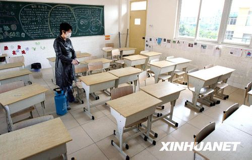 10月30日,上海市梅陇中心小学的卫生老师对出现一名感冒症状学生而封闭的教室进行消毒。