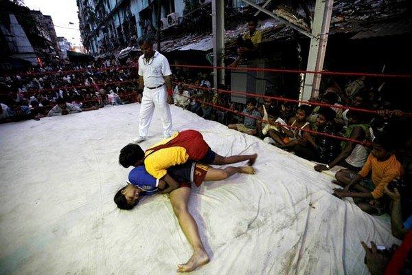 女子摔跤:在印度加尔各答路边一个临时搭建的拳击台上,两名女子摔跤手正在进行一场业余比赛。这些比赛是排灯节庆祝活动的一部分。