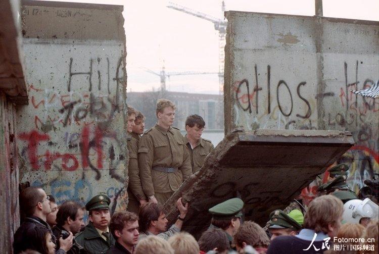 1989年11月11日,德国,柏林:德国边防军对游行示威者推倒勃兰登堡门墙段的漏洞视而不见。