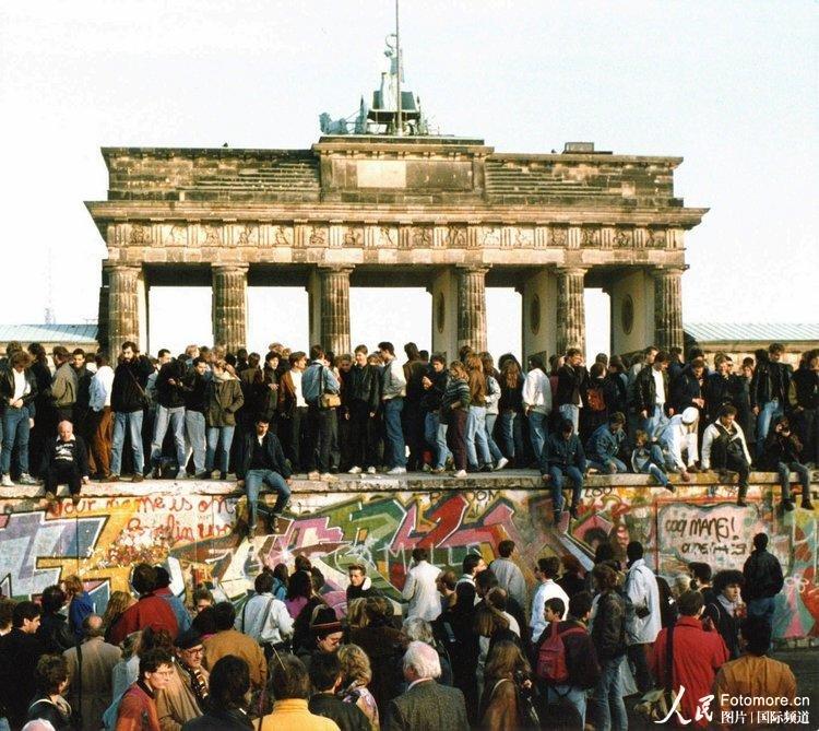 1989年11月10日,德国,柏林:柏林墙开放第二天,来自东西部的德国人站在勃兰登堡门前的柏林墙上。