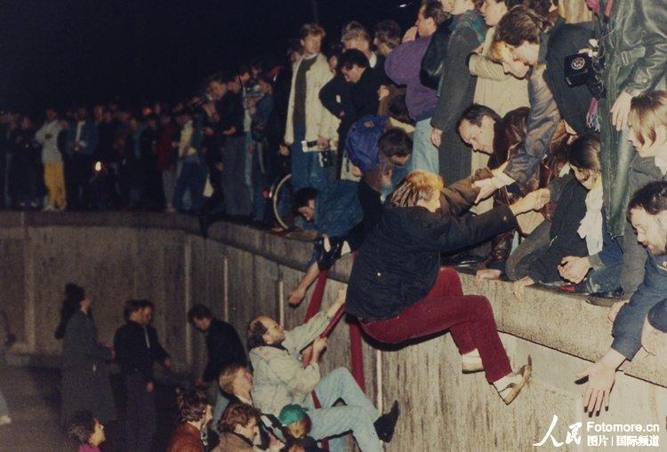 1989年11月10日,德国,柏林:西德市民帮助东德市民爬过柏林墙。