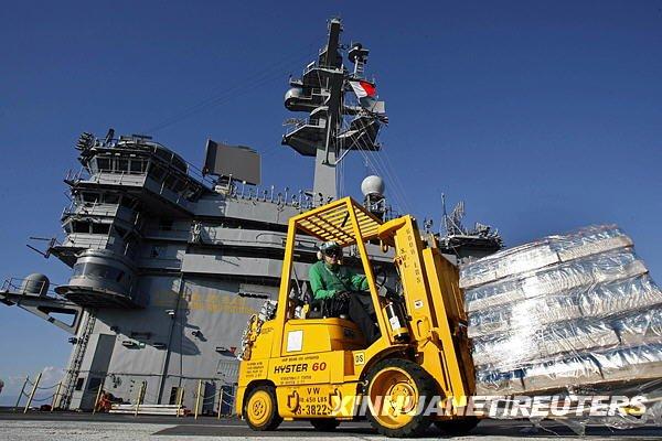 """在美军""""卡尔·文森""""号航空母舰的甲板上,救援人员搬运瓶装水。"""