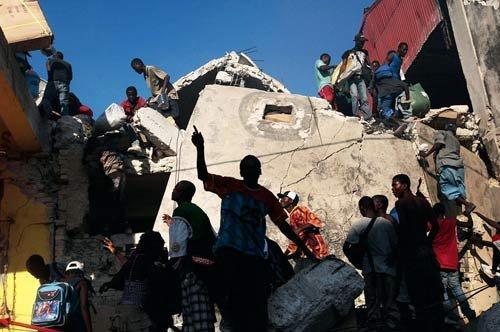 大量民众在瓦砾中抢夺曾经商店中的商品,当地一片混乱