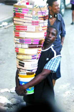 1月20日,太子港,一名海地居民在街头卖药。新华社发(乌巴尔多·冈萨雷斯摄)