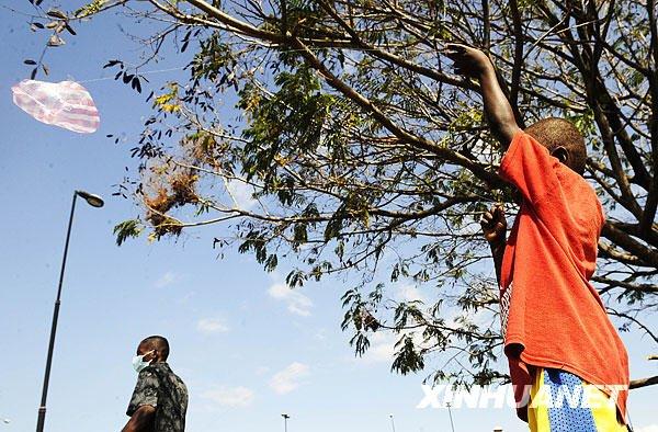"""2月1日,在海地首都太子港一个临时灾民安置点,一名少年放飞用塑料袋制作的""""风筝""""。"""