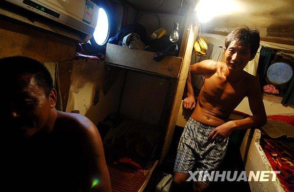 2月3日,在印度尼西亚马鲁古省图阿尔岛的一个港口,两名中国渔民在船上狭小的卧室休息。