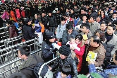 大量旅客通过检票口准备上车,警察用喇叭提醒乘客按秩序进站。本报记者董世彪摄