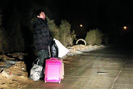 """八成唐家岭""""蚁族""""节前返乡 村民短租房屋。图为一名租房者正在路边等车,准备返乡。 摄/法制晚报 记者 王丹"""