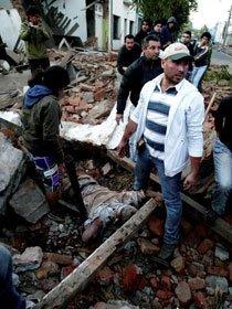 人们站在一位地震遇难者旁边