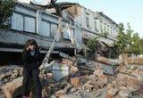 居民坐在倒塌的房屋废墟上