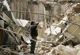 一名男子站在一片楼房坍塌后的废墟中