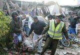 警察和当地的居民从废墟中抬出一位地震伤员