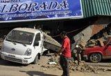 两辆汽车被在地震中坍塌的房屋损坏