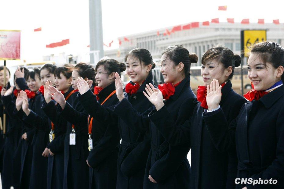 3月2日,礼仪小姐在首都机场等候迎接抵京参加全国两会的代表、委员。中新社 发 杜洋 摄