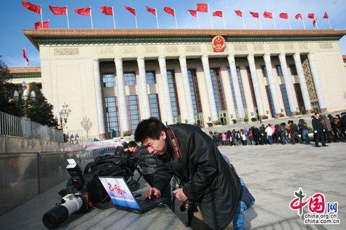 """人民大会堂前记者争分夺秒报""""两会""""(图)"""