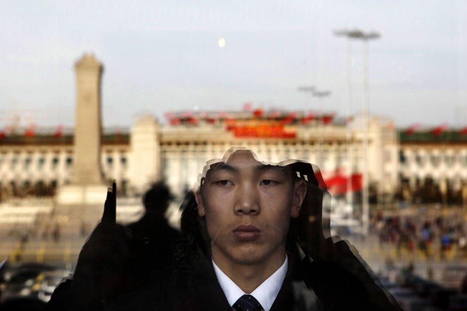 3月2日,北京人民大会堂,一名安保人员透过落地窗往外张望,玻璃上反射出红旗招展的天安门广场。