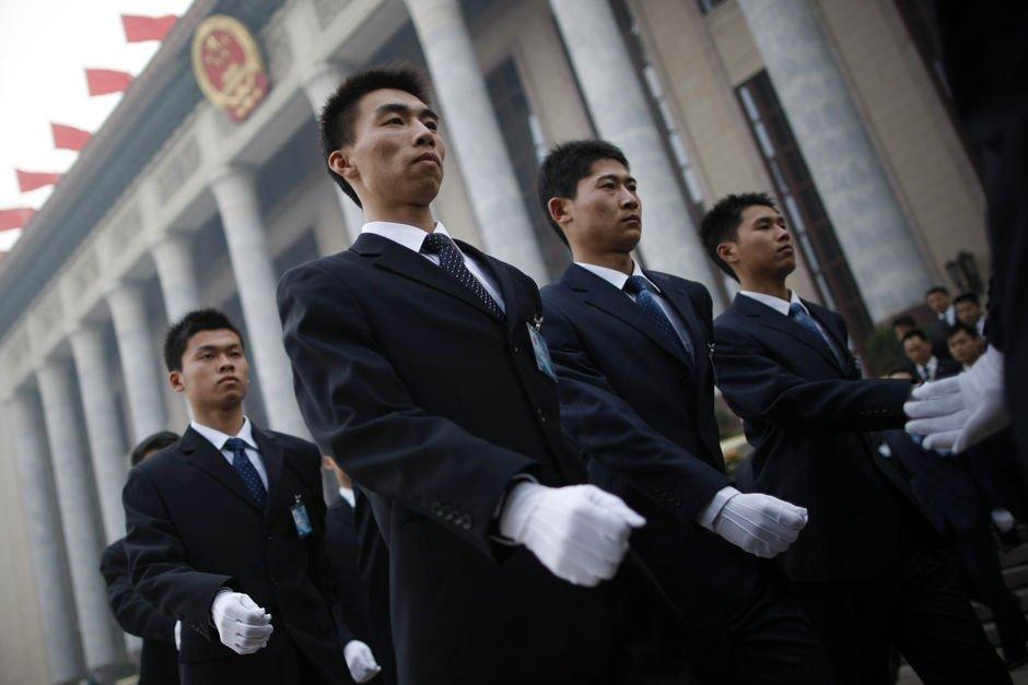 3月3日,身着黑色西装的工作人员正在排队进入人民大会堂,西方媒体普遍猜测这些黑衣工作人员的身份是特警。
