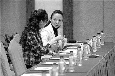 每天提早到场的邰丽华委员和手语翻译进行交流。本报记者王铮摄