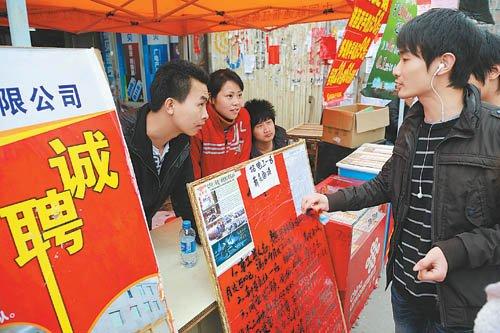 一名新生代农民工在向企业招工人员咨询工资待