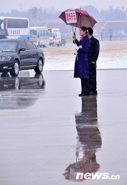 图为服务人员在雪中等待代表返回驻地。新华网 孙巍 摄