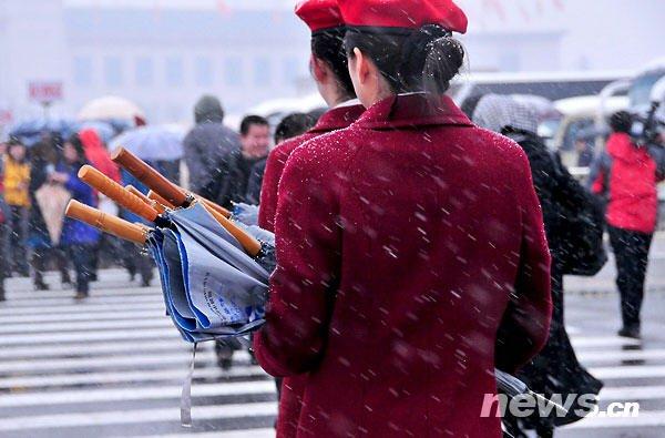 图为服务人员手拿雨伞在雪中行走。新华网 孙巍 摄