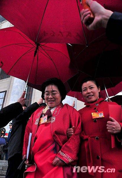 图为两会代表结束会议后步出人民大会堂,工作人员为其撑起雨伞。 新华网 孙巍 摄