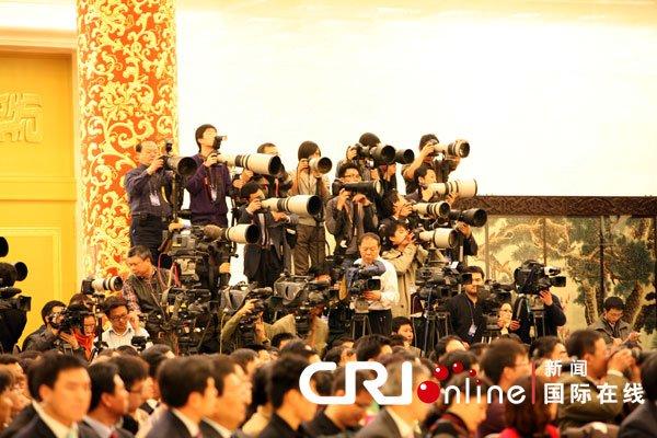 """14日上午,中国总理温家宝在人民大会堂出席记者招待会并回答记者提问。大量的中外摄影记者在会场展开了一场名副其实的""""摄影新闻战""""。正对主席台的有利位置聚集的摄影摄像记者最多 (常昕摄)"""
