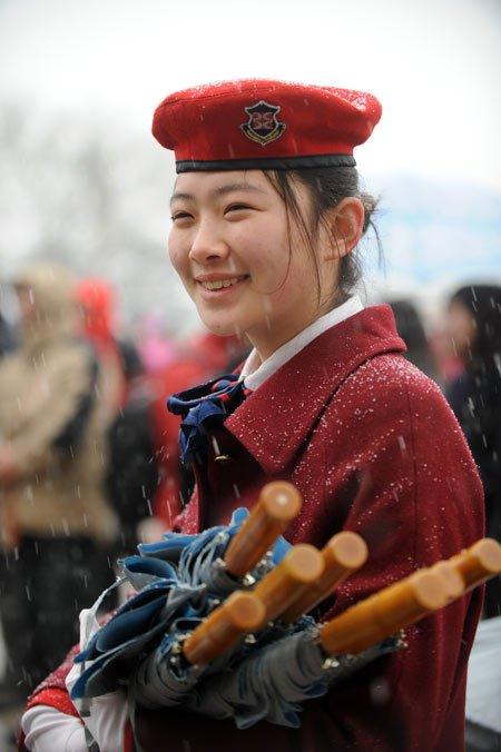3月14日,第十一届全国人民代表大会第三次会议在北京人民大会堂举行闭幕会。北京下起了雨夹雪,一名来自代表驻地的服务员抱着雨伞在人民大会堂前迎候代表。