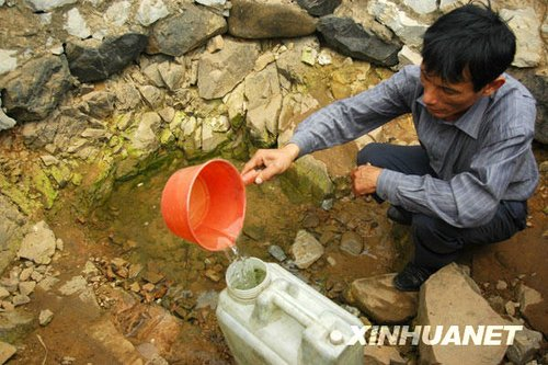 3月24日,在广西上思县叫安乡文明村,村民梁胜欣在一口快要干涸的水井里取水。新华社发(梁富盈 摄)