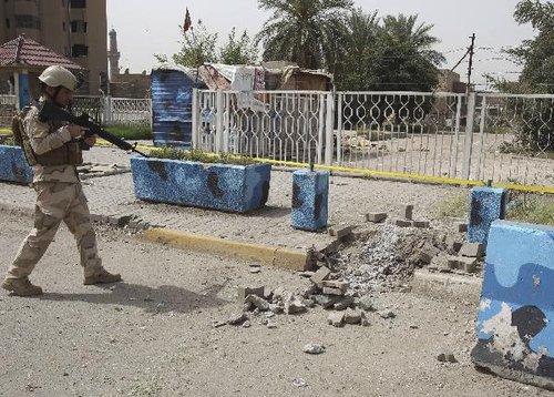 4月4日,在伊拉克首都巴格达,一名安全部队士兵检查爆炸现场。伊拉克首都巴格达4日上午发生3次剧烈爆炸,中国驻伊拉克大使馆和新华社巴格达分社办公室遭到波及,建筑物受损。目前没有中方人员伤亡的消息。新华社/路透