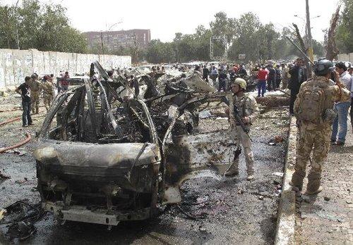 4月4日,在伊拉克首都巴格达,一些市民和伊安全部队人员聚集在爆炸现场周围。新华社/路透